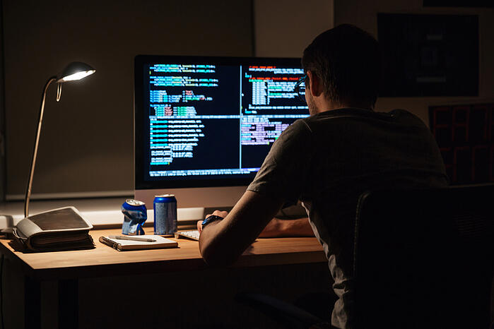 Back view of modern programmer sitting and writing code in dark room-1